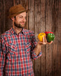 Happy farmer holding peppers on rustic wood