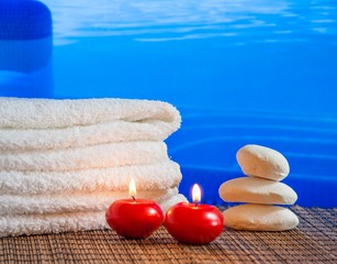 Spa massage with towel stacked candles near swimming pool