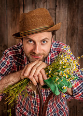 Happy farmer holding camomile flowers