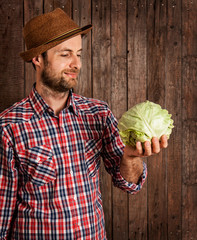 Happy farmer holding cabbage on rustic wood