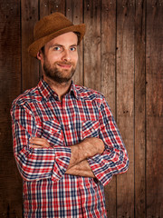Happy farmer standing on rustic wood background