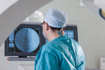 the surgeon at the monitor in the operating room