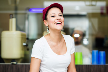 Young happy saleswoman portrait inside ice cream shop.
