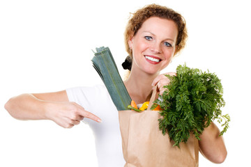 woman pointing at a bag full of vegetables