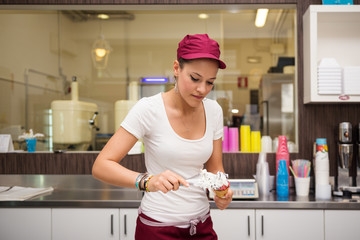 Young beautiful sales woman portrait preparing ice cream cup.
