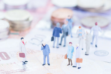 Miniature business people on UK banknotes