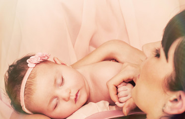 young beautiful mother holding with love her little cute sleepin