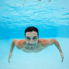 Smiling underwater man portrait inside swimming pool.