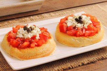 Bruschetta with tomatoes, capers, oregano and cheese