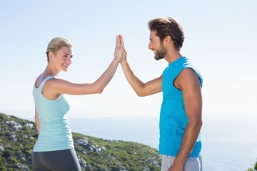 Fit couple standing high fiving