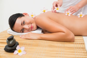 Beautiful brunette enjoying a flower back massage