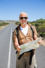 Handsome hiker holding map and smiling at camera