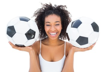 Pretty girl holding footballs and laughing at camera