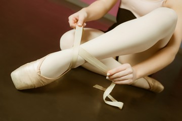 Ballerina tying the ribbon on her ballet slippers