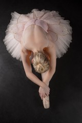 Graceful ballerina bending forward in pink tutu