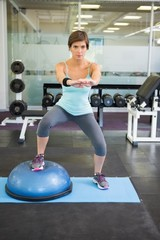 Fit brunette using bosu ball for squats