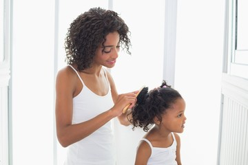 Pretty mother brushing her daughters hair
