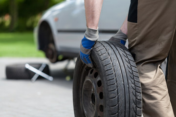 Man rolling a spare wheel