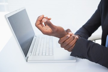 Businessman holding his sore wrist from typing