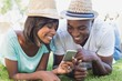 Happy couple lying in garden together looking at smartphone