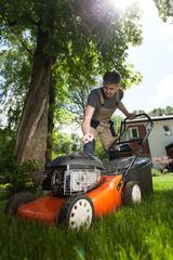 Man cutting grass in his yard