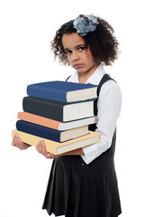 Unhappy school girl with pile of books