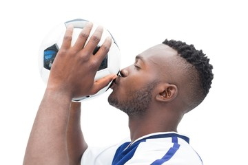 Football player in blue kissing ball