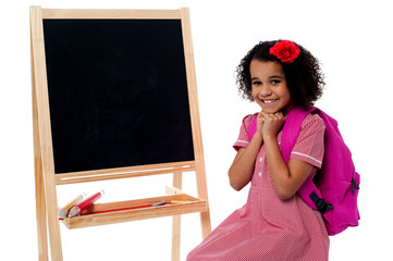 Pretty girl sitting near blank chalk board