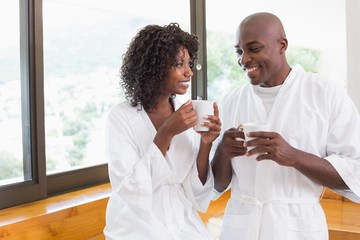 Happy couple having coffee together in bathrobes