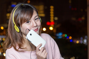 Beautiful young Asian woman wearing yellow headphones