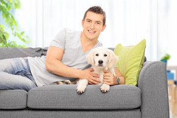 Man lying on a couch with a Labrador puppy at home