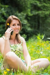 Relaxed woman using mobile phone in field
