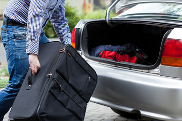 Man putting suitcases in car trunk for a journey