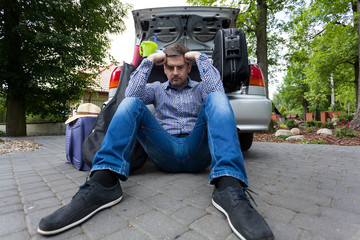 Upset man and car full of luggage bags
