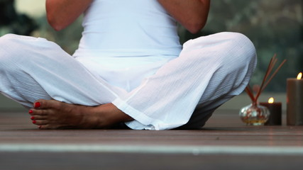 Woman in white sitting in lotus pose