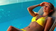 Gorgeous blonde in bikini lying on deckchair poolside