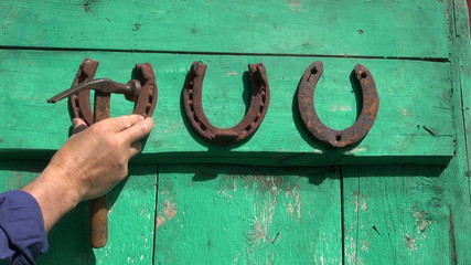 hammering antique rusty horse shoe luck symbols on  door