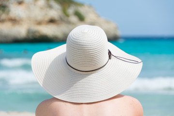 Woman with hat on the beach