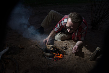Man making firecamp outdoors at night.