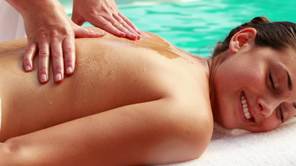 Beauty therapist massaging oil into womans back