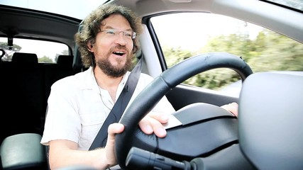Happy man talking on the phone while driving