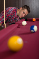 Young man playing billiard