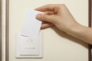 Hotel keycard - Female hand puts keycard into switch.