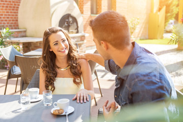 Young couple talking on the terrace of the restaurant