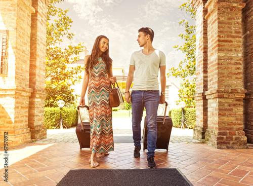 Leinwanddruck Bild Young couple standing at hotel corridor upon arrival