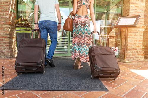Leinwandbild Motiv Young couple standing at hotel corridor upon arrival