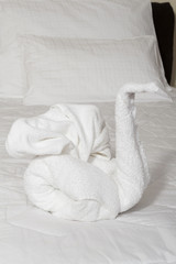 Towel swan - Swan made from towels on bed .