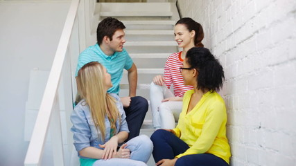 smiling students sitting on stairs and talking