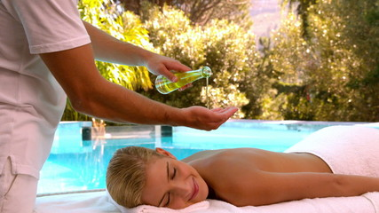 Masseuse pouring oil onto hands for massage