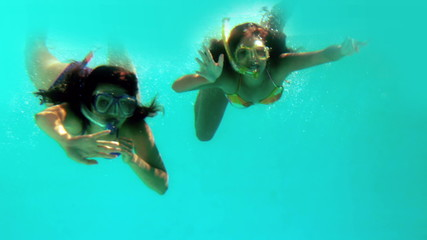 Happy friends waving at camera underwater wearing snorkels